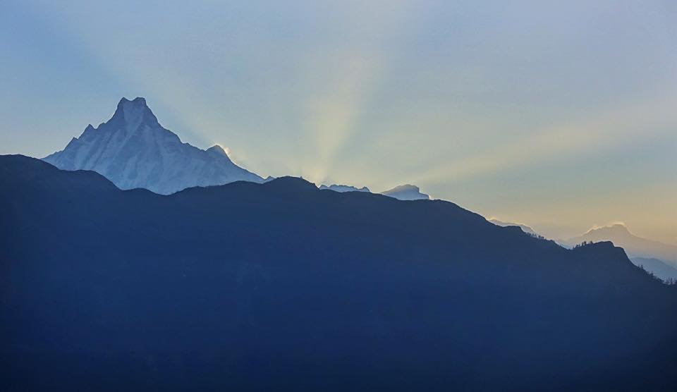 Rays of sun shine from behind a mountain with a fish-tail shaped peak at sunrise