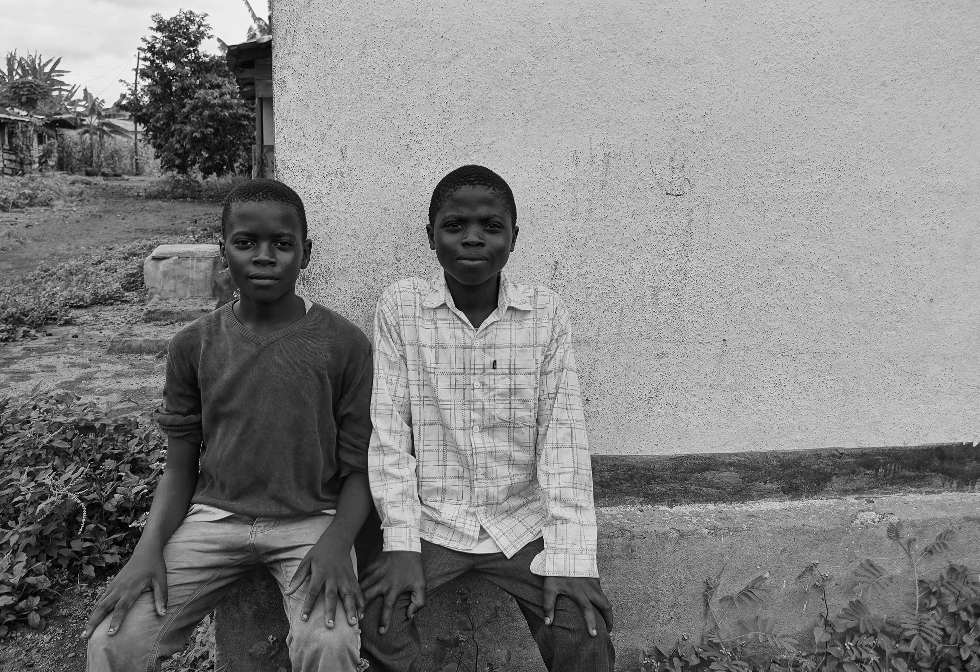 Two boys sit on a ledge in front of a white wall looking at the camera