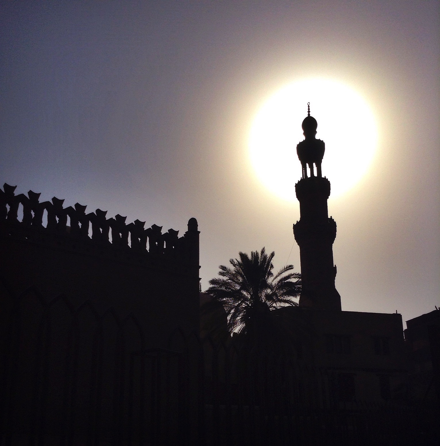 A minaret of a mosque silhouetted with the sun directly behind it