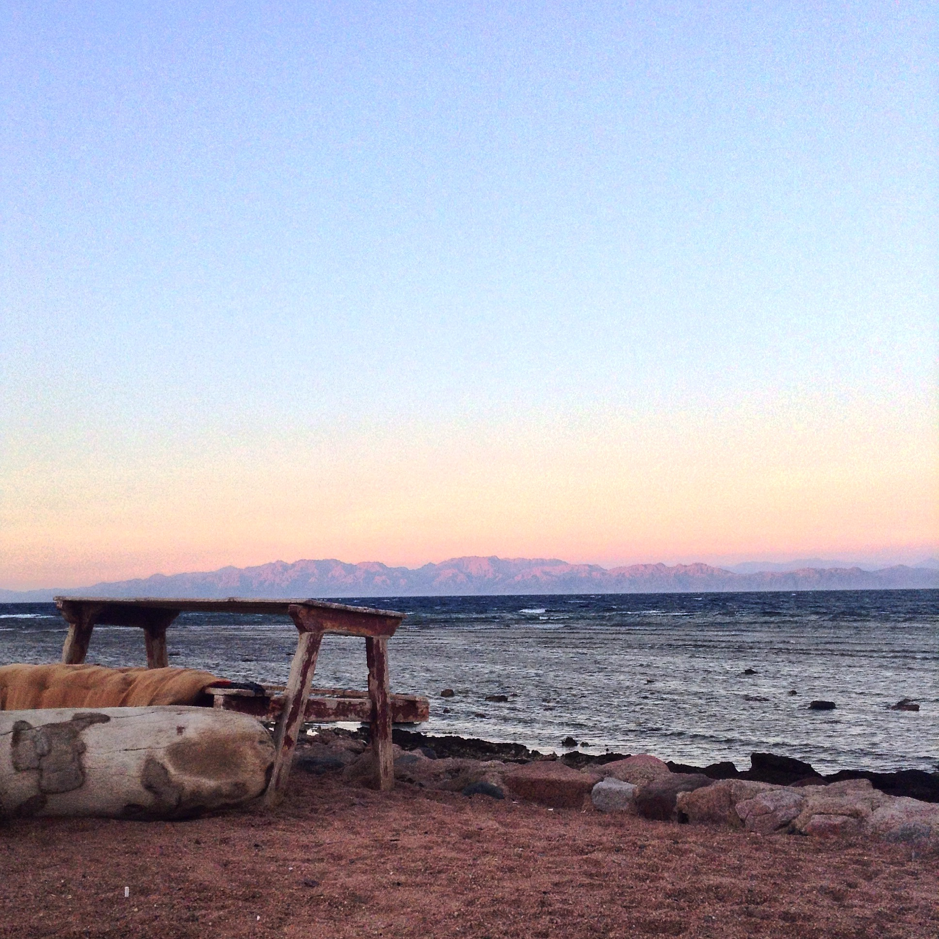 A picnic table on a beach with the pastel colors of a sunset in the background with mountains on the other side of the Red Sea