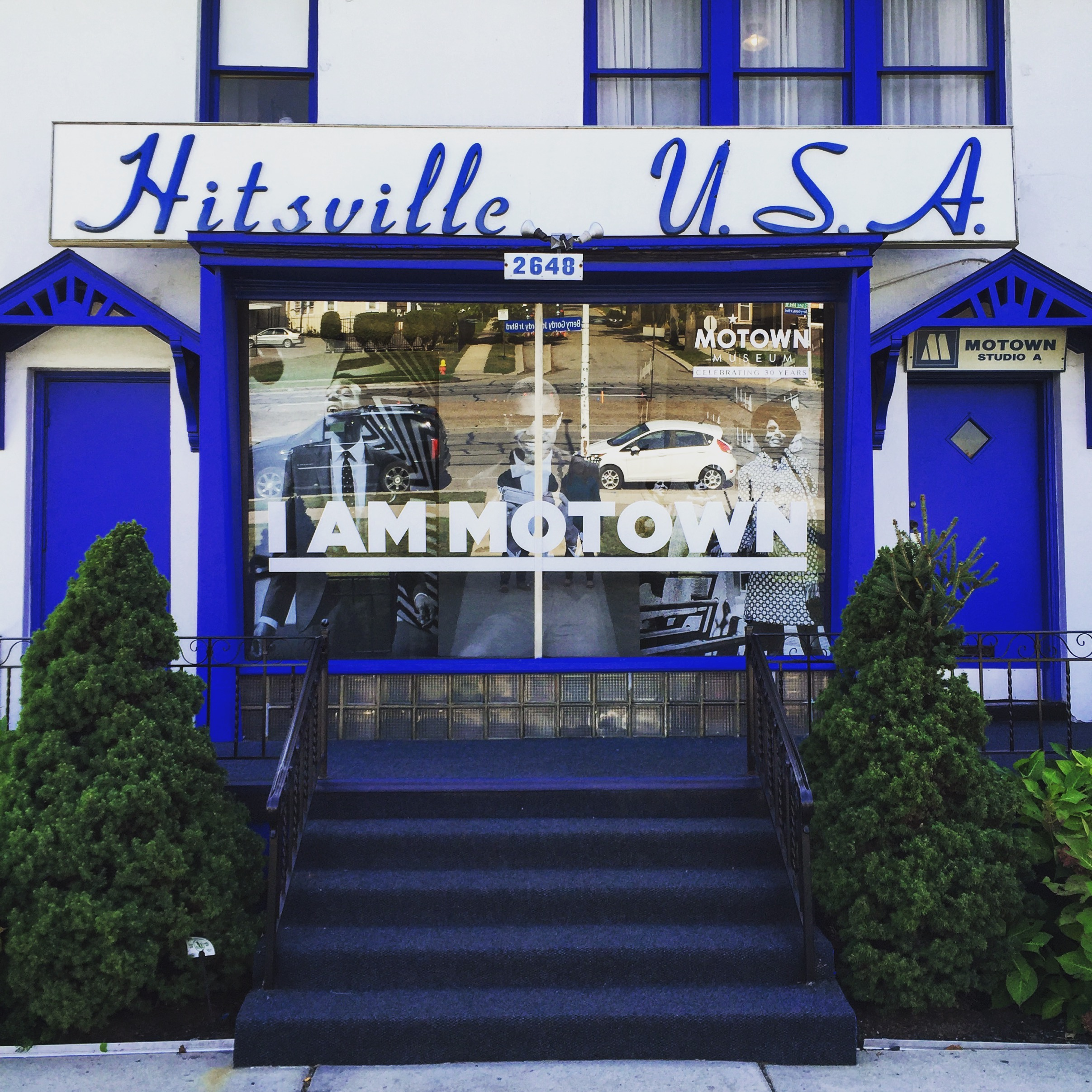 The front of a white house with blue doors and trim and the words Hitsville, USA on a sign