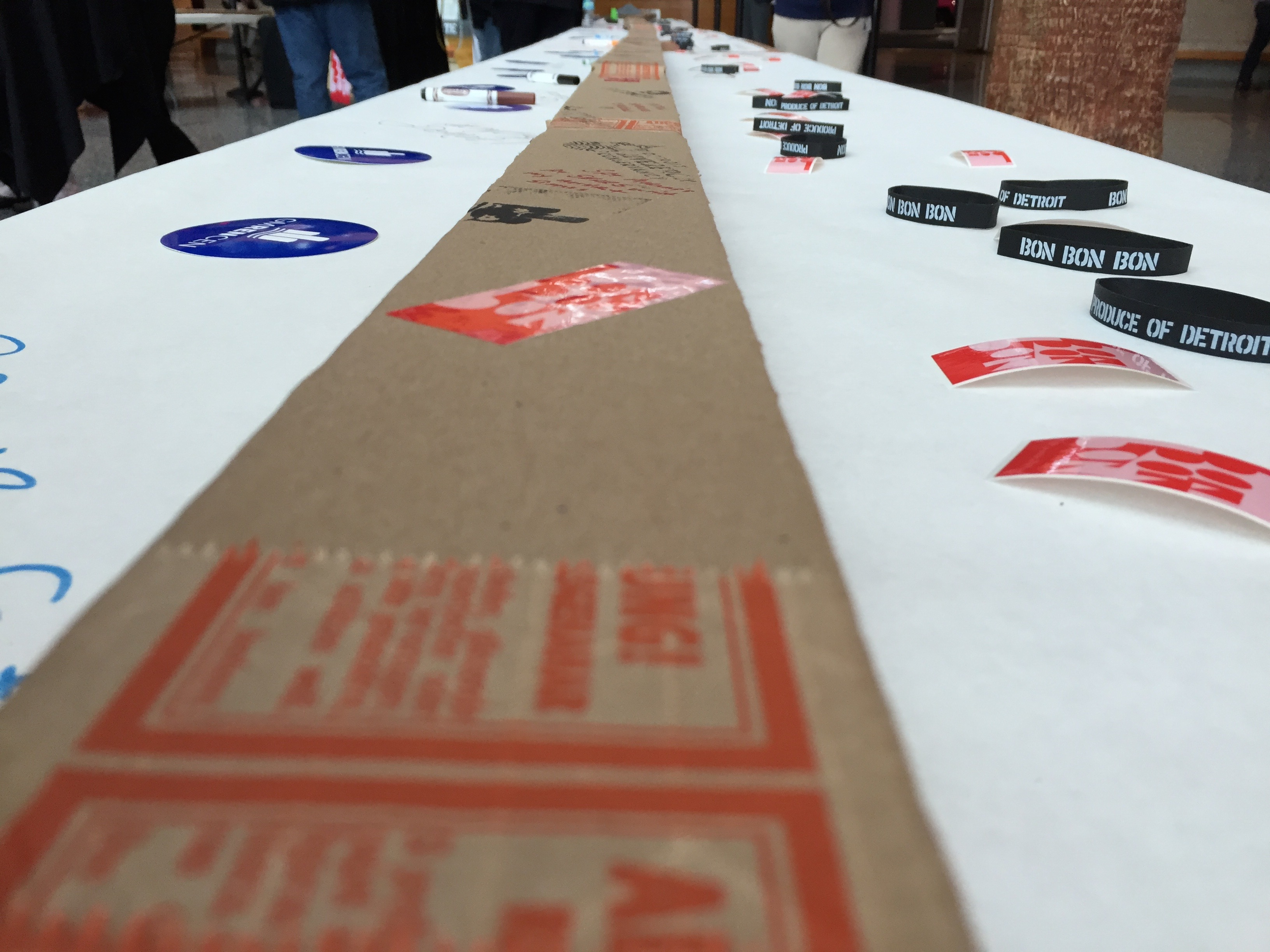 A long card board box on a table with white paper going into the distance