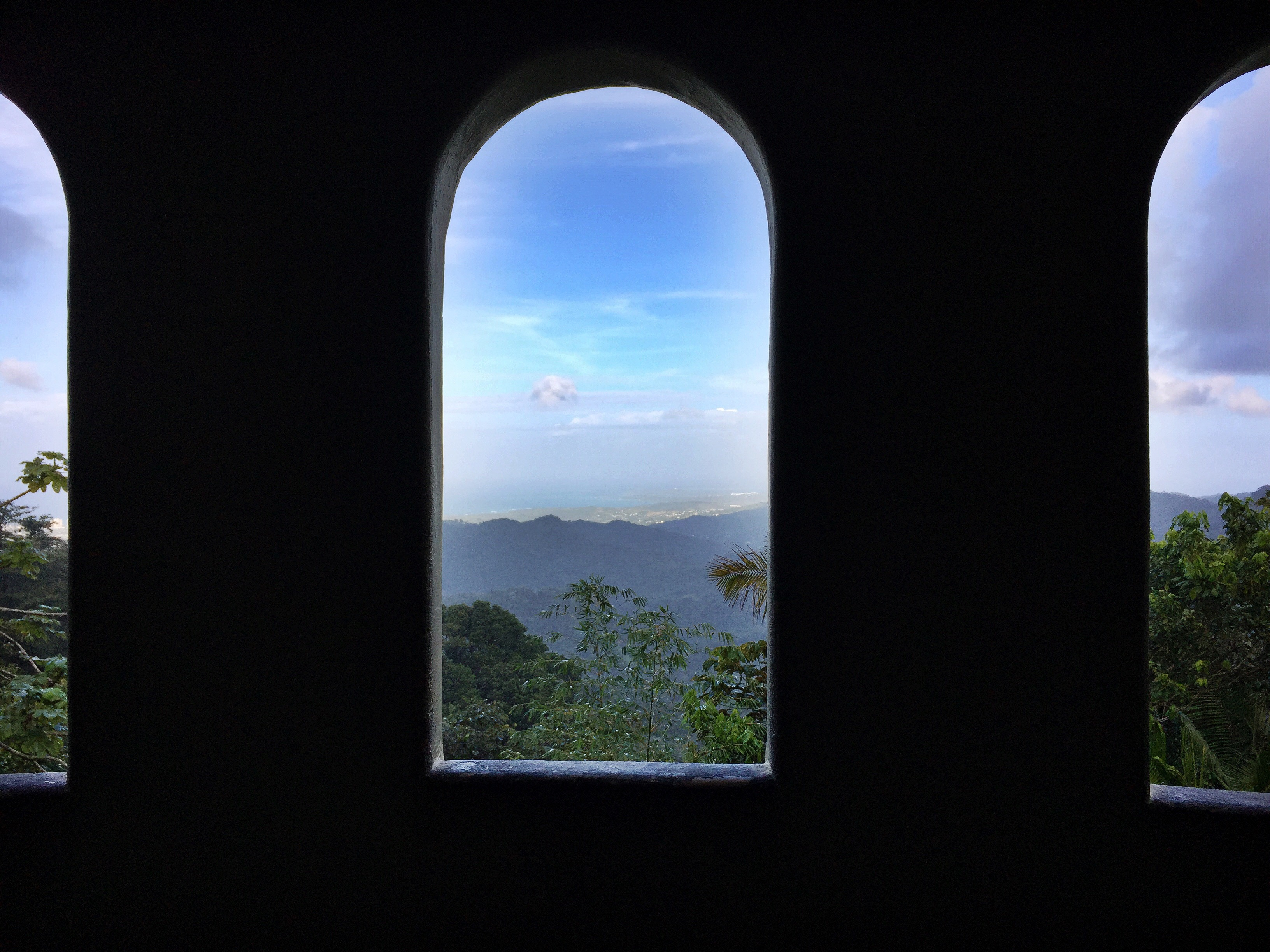 View of the El Yunque Rainforest through an arched window of a tower