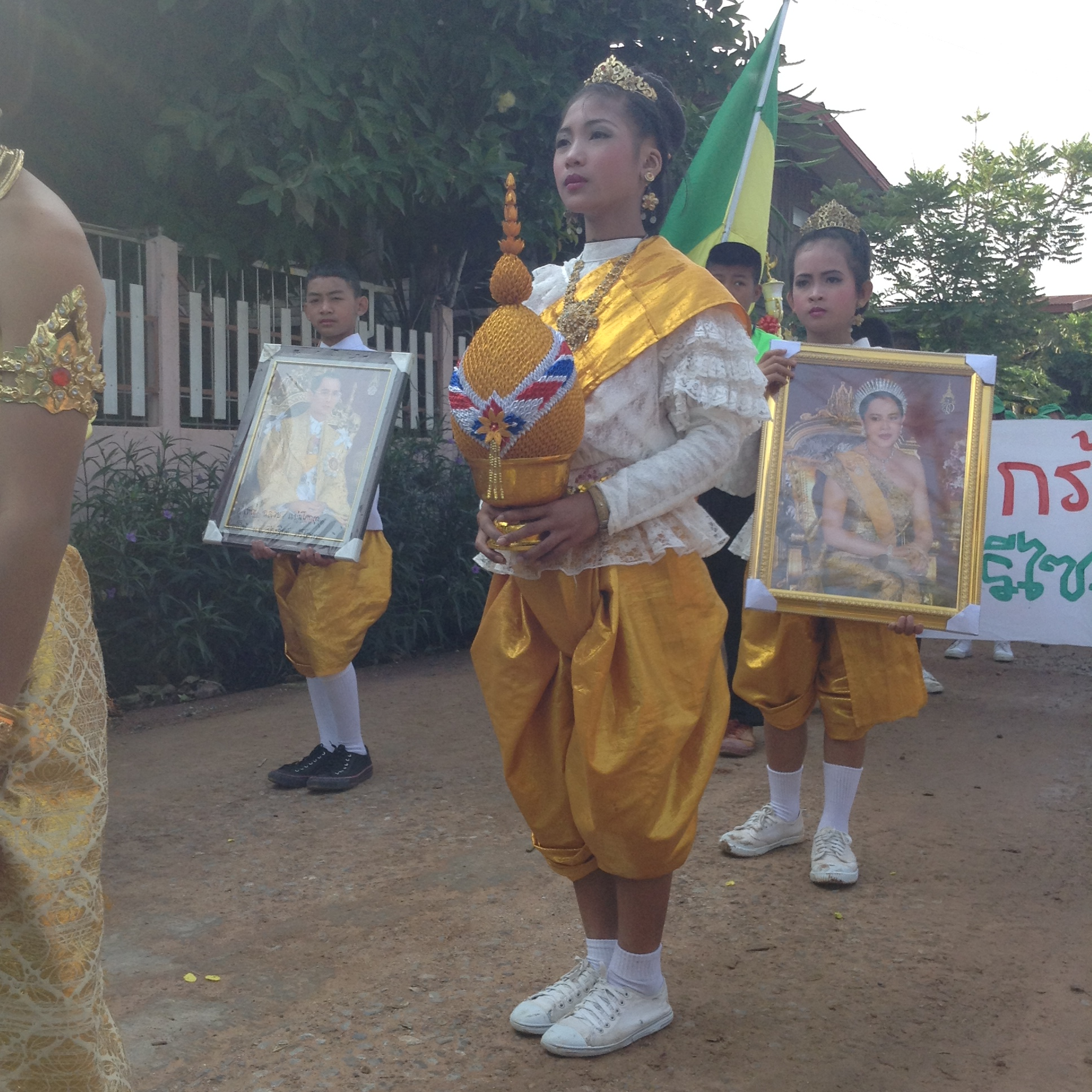 young thai children wearing traditional clothing carrying pictures of the thai king and queen