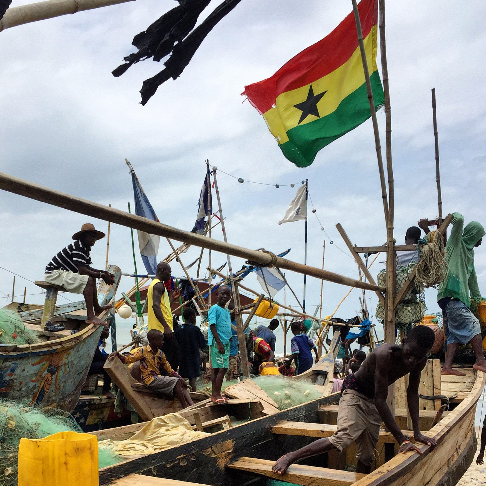 a few people standing on beached wooden fishing boats with flags flying above