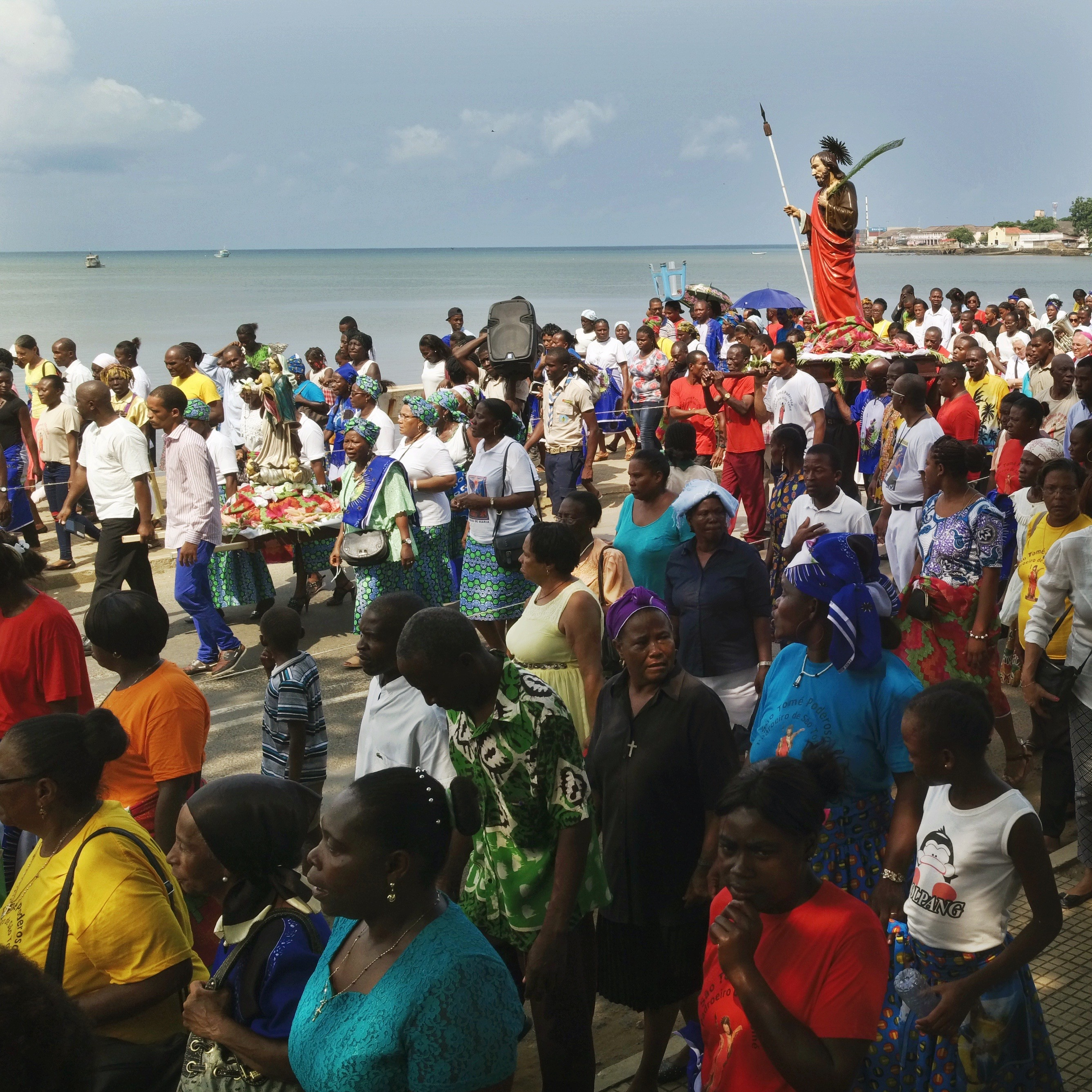 a crowd of people around a statue of st thomas parading on a street in front of the ocean