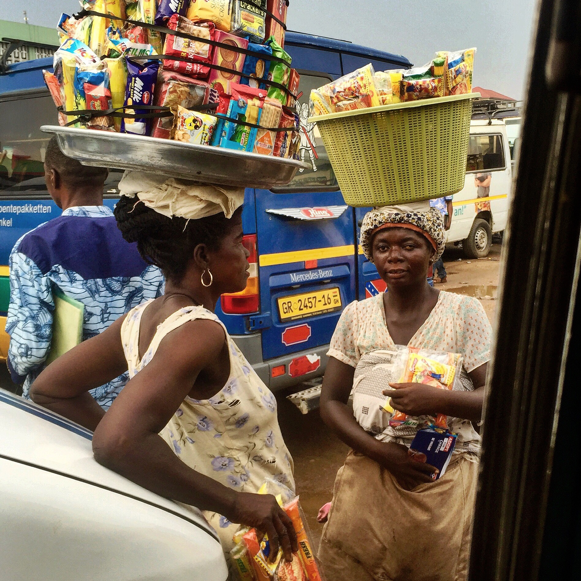 Two women talking with baskets on their heads filled with packets of crackers and cookies