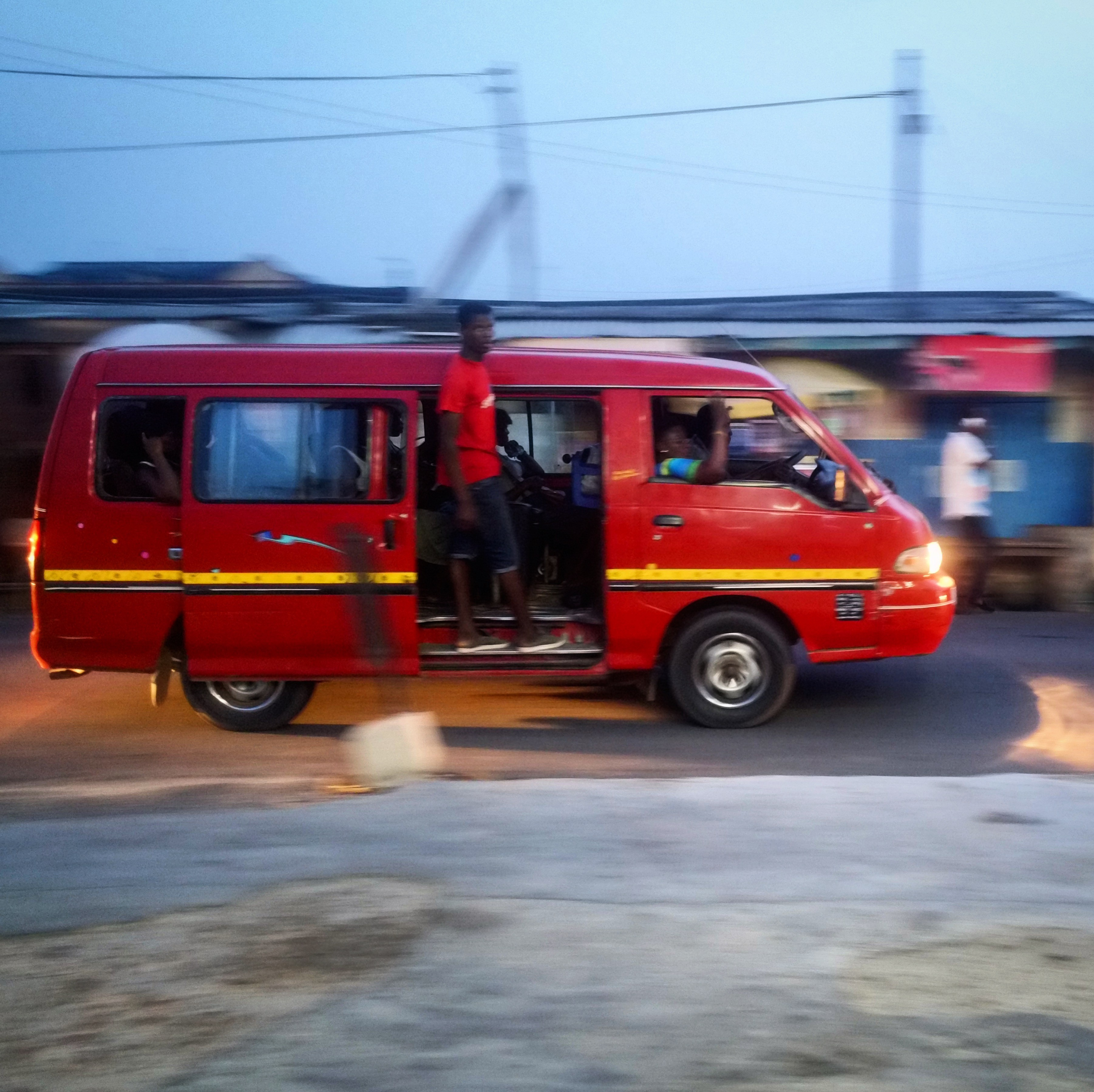 A red van, with the side door open and a young man standing and hanging off the vehicle, is moving from left to right.