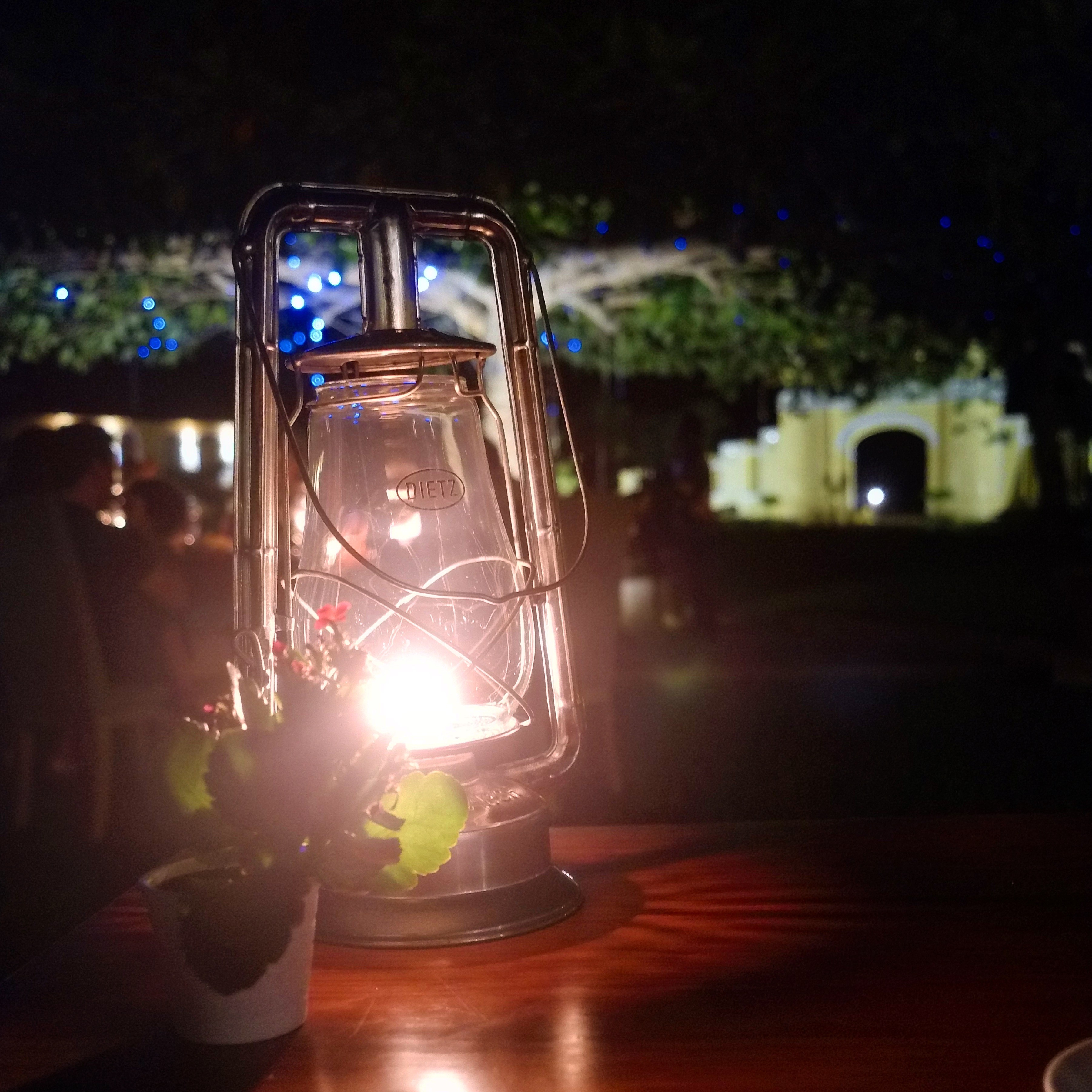 A close-up of a lantern on a table at night, with the entrance to the property out of focus in the background.