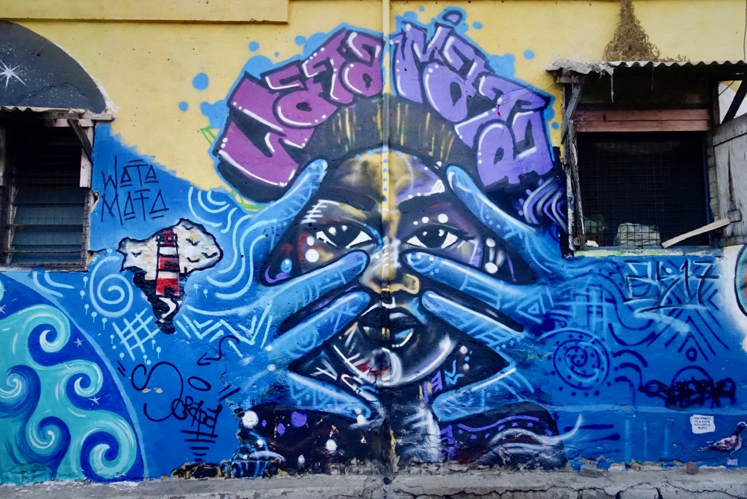 "A mural of a woman with blue hands held in front of her face under the words ""Wata Mata"""